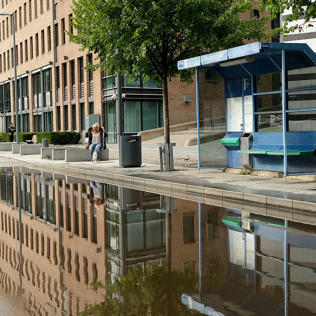 Après l'orage, femme ayant le gout du risque en attendant le bus